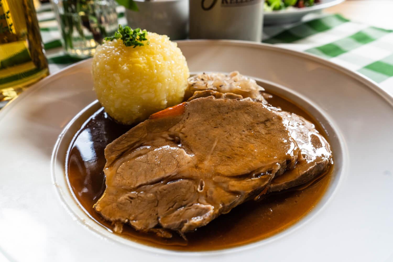 A slice of roast pork with a potato Knödel, German boiled dumpling, in a pool of gravy.